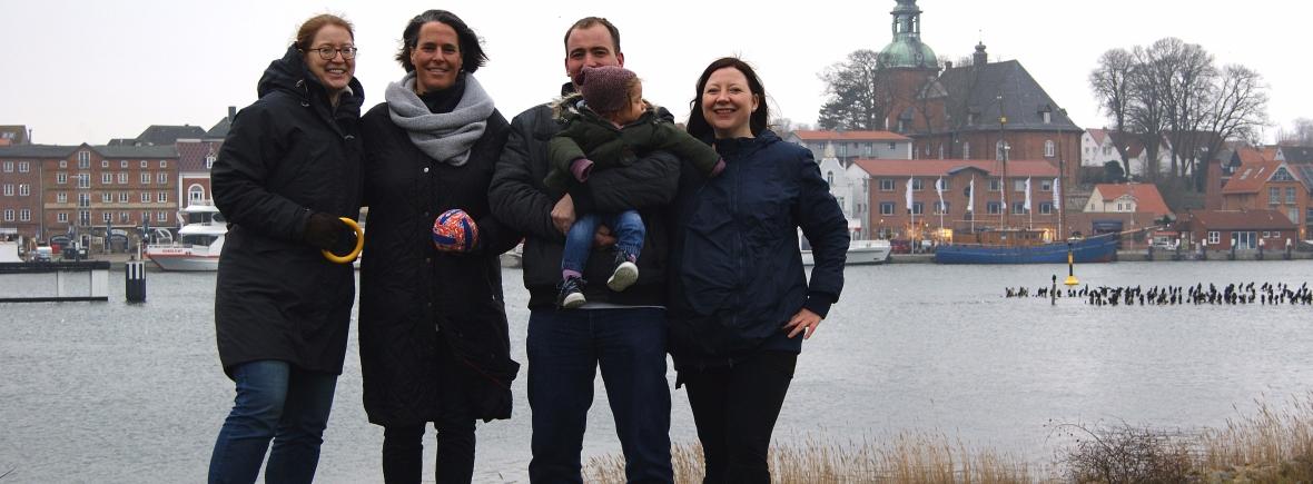 Fünf Personen stehen vor einem Fluss und den städtischen Sehenswürdigkeiten