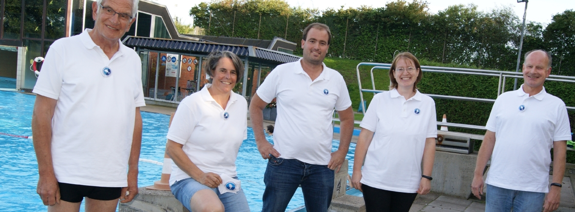 Drei Männer und zwei Frauen stehen vor einem Schwimmbecken