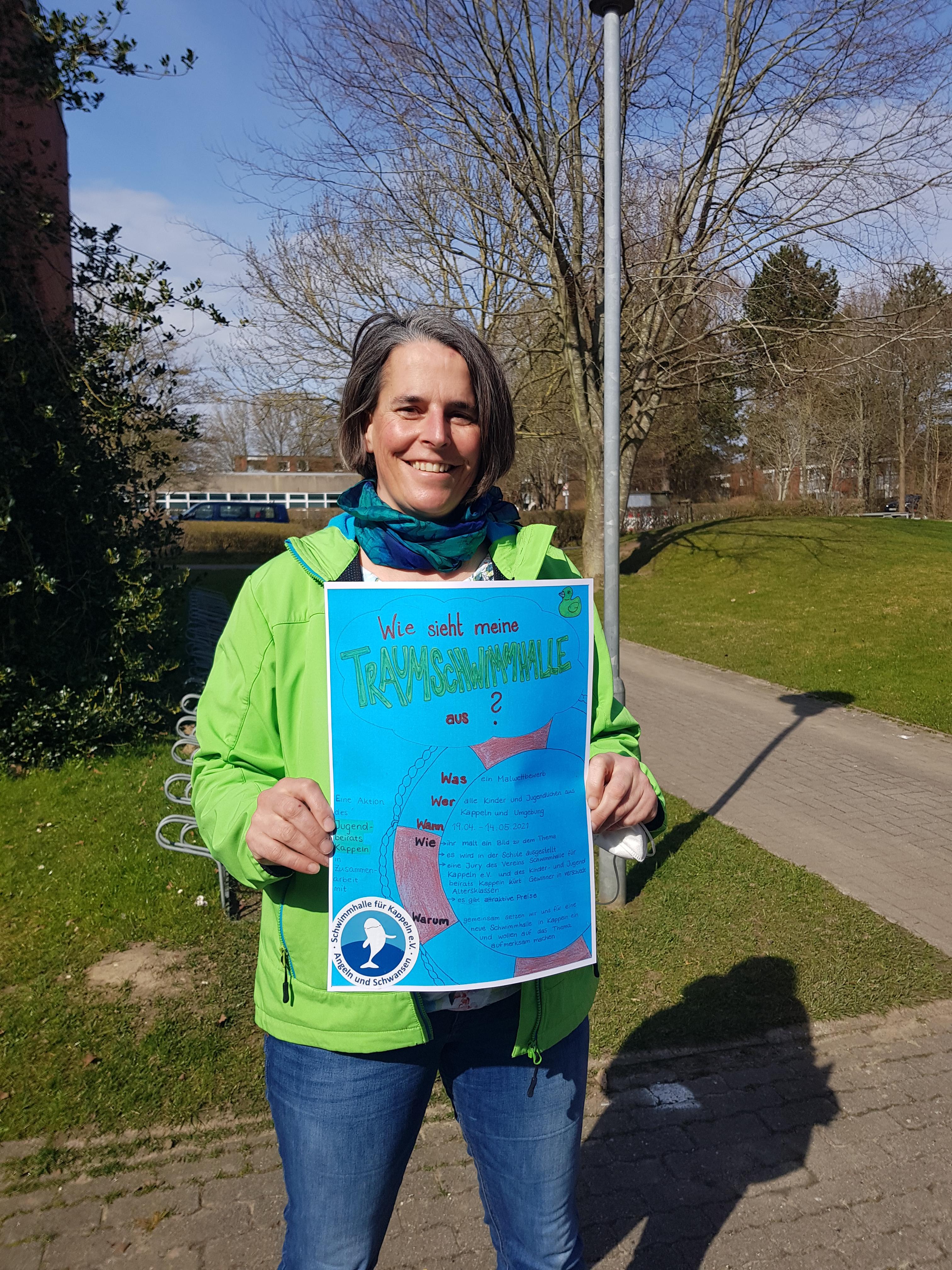 Eine Frau zeigt ein Plakat für einen Schülermalwettbewerb in die Kamera