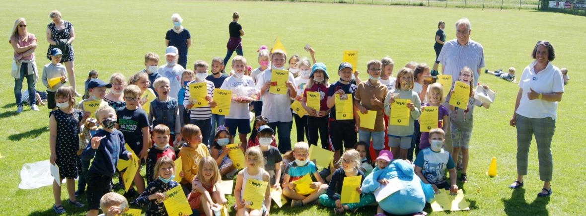 Viele Kinder auf einem Sportplatz, die ihre Urkunden und Gewinne zeigen