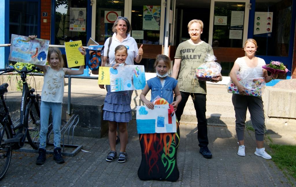 Drei Schülerinnen zeigen ihre gemalten Bilder und Urkunden, neben ihnen stehen zwei Lehrer und Swantje Schmagold-Trocha vom Schwimmhallenverein